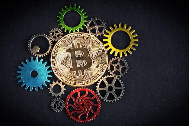 Golden bitcoin glowing among colorful cog wheels