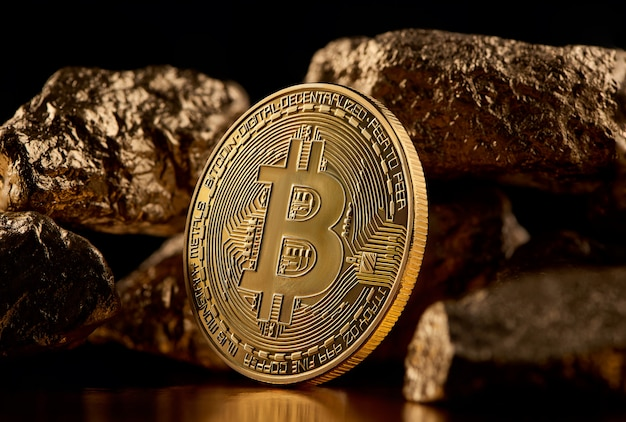 Golden bitcoin and gold lumps representing futuristic world trends both isolated on black background