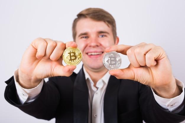 Золотой биткойн в руке человека, цифровой символ виртуальной криптовалюты.