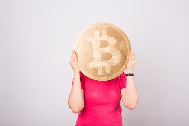 女性の手の黄金のビットコイン、仮想暗号通貨のデジタルシンボル。