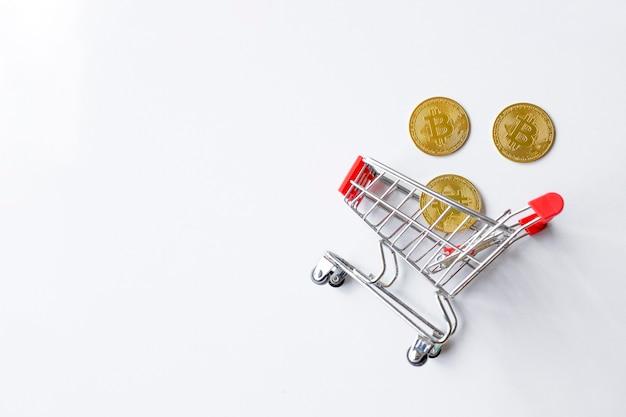 白いテーブルの背景の上のショッピングカートの黄金のビットコイン。上面図