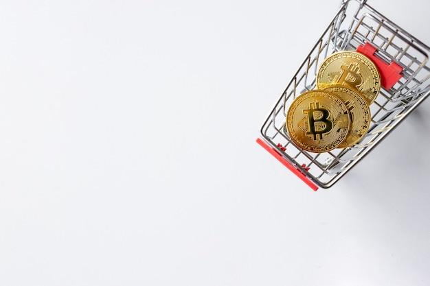 Золотой биткойн в корзине на белом фоне таблицы. вид сверху