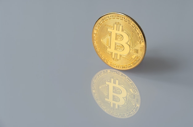 Golden bitcoin isolated on gray surface