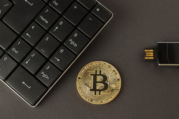 Golden bitcoin, keyboard and flash drive on a dark background top view