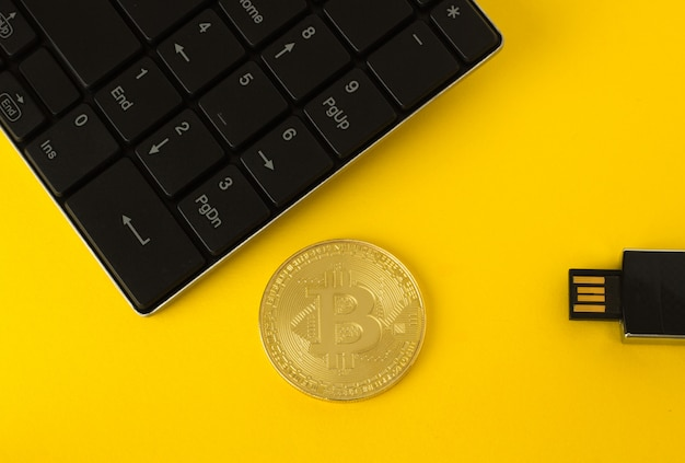 Golden bitcoin, keyboard and flash drive on a yellow background top view