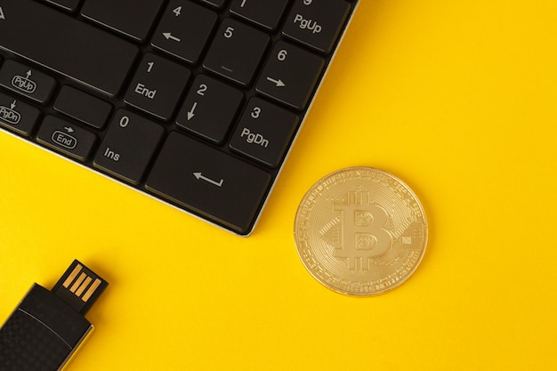 Golden bitcoin, keyboard and flash drive on a yellow background