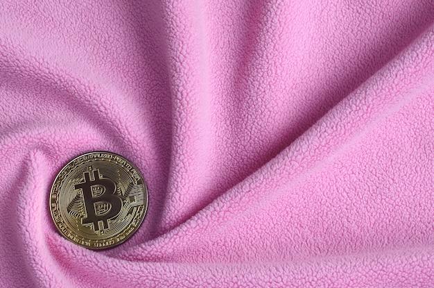 The golden bitcoin lies on a blanket made of soft and fluffy light pink fleece fabric