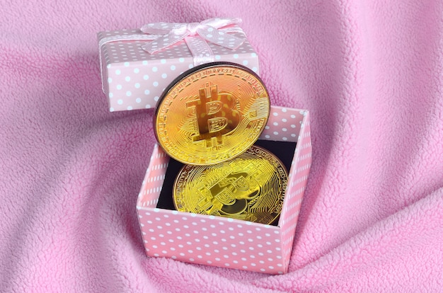 The golden bitcoin lies in a small pink gift box with a small bow on a blanket