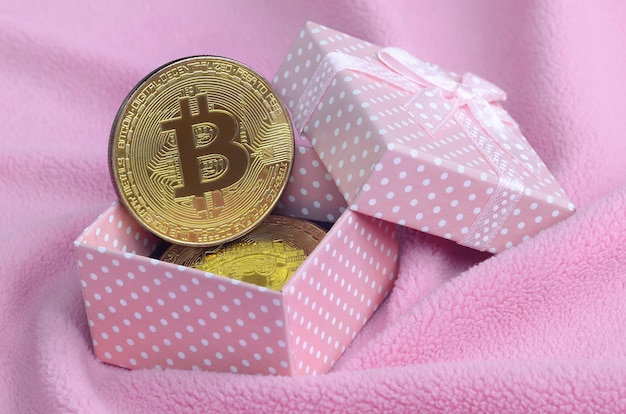 The golden bitcoin lies in a small pink gift box with a small bow