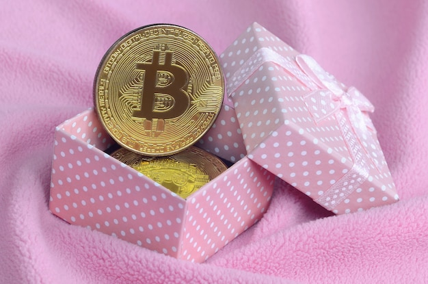The golden bitcoin lies in a small pink gift box with a small