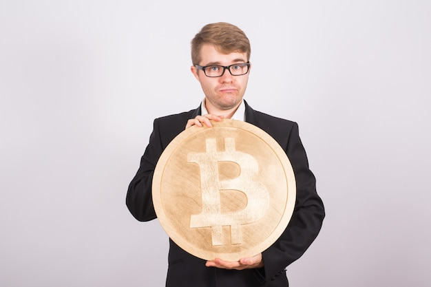 Golden bitcoin in a man hand, digital symbol of a virtual cryptocurrency.