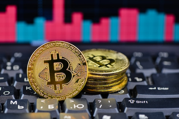 Golden bitcoin on notebook keydoard with chart on background