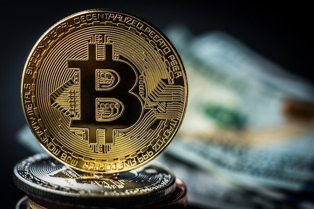 Золотой биткойн на куче металлических монет