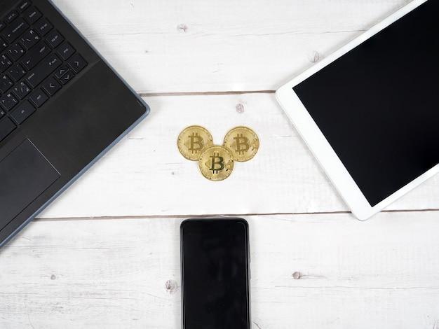 トップビューのデジタルマネーの概念の周りのラップトップタブレットとスマートフォンと机の上の黄金のビットコイン