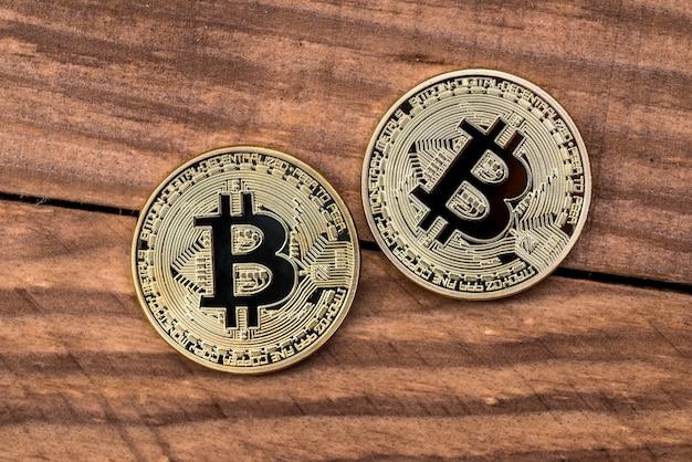 나무 책상에 황금 bitcoin입니다. 확대
