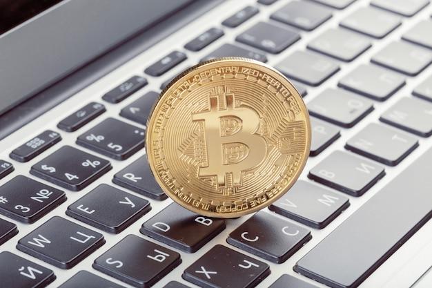 Золотая монета биткойн на клавиатуре