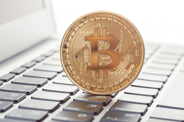 Золотой биткойн символ физической монеты на клавиатуре