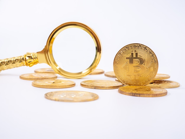 Golden bitcoin replica and magnifying glass on white   background.business and finance concept.