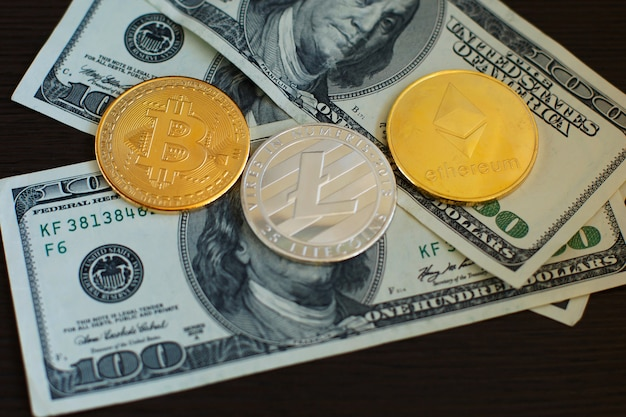 Golden bitcoin, silver litecoins and ethereum on us dollars close up.