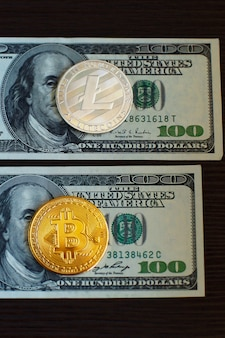 Golden bitcoin and silver litecoins on us dollars close up.