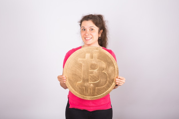 Golden bitcoin in a woman hand, digital symbol of a virtual cryptocurrency.