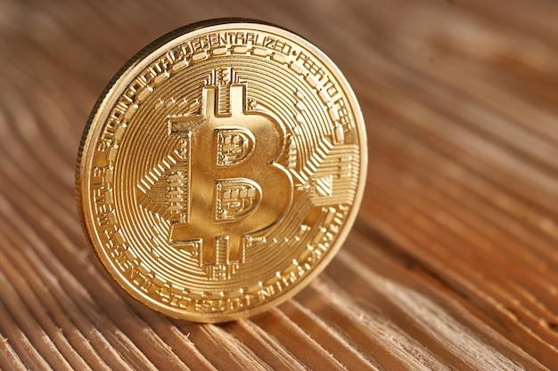 Golden bitcoin on wood
