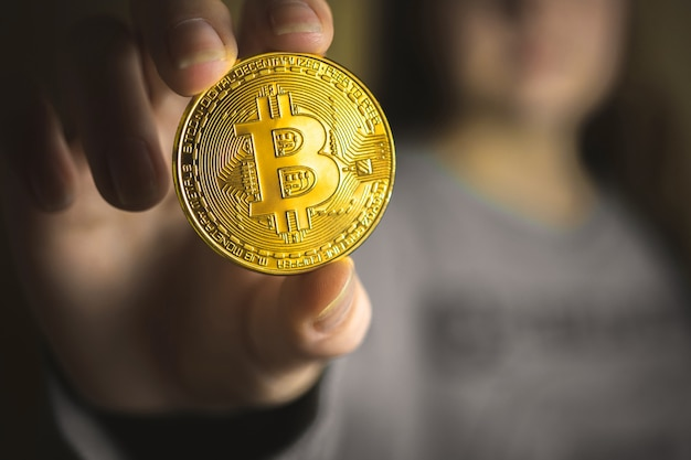 Golden bitcoin in young woman hand, close-up view of crypto currency, business, online virtual future currency concept photo