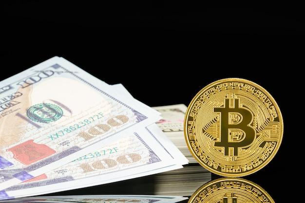ゴールデンビットコインと100ドルの米国紙幣。金属の光沢のあるビットコイン暗号通貨コインと米ドルのクローズアップ