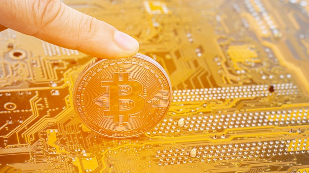 Golden bitcoins on circuit board.electronics finance and trading .
