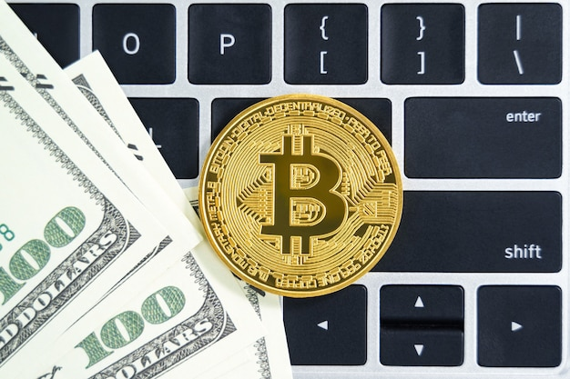 ゴールデンビットコインコインと米国紙幣のキーボードコンピューター。金属の光沢のあるビットコイン暗号通貨コインと米ドルのクローズアップ