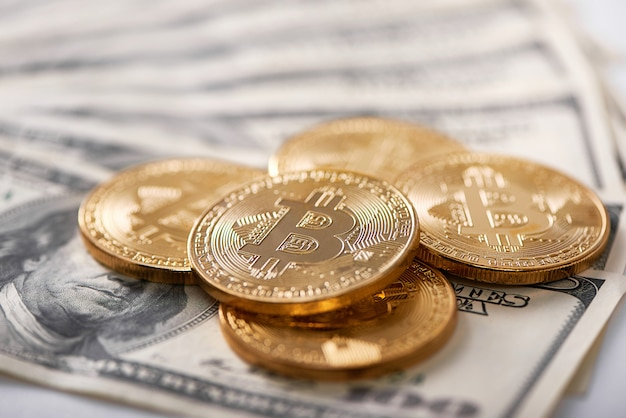Golden bitcoins on dollar banknotes
