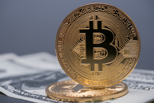 Golden bitcoins on dollar bills