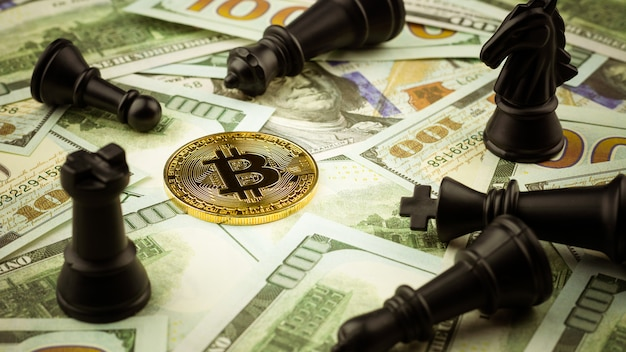 Golden bitcoins on dollars bills and a pile of lose chess