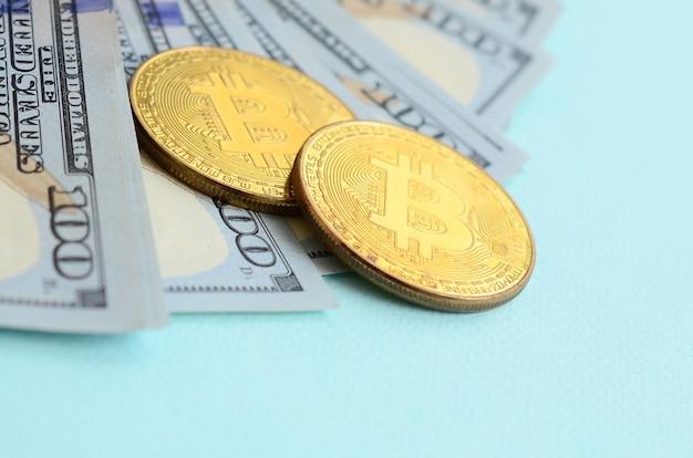 Golden bitcoins and hundred dollar bills lies on light blue background