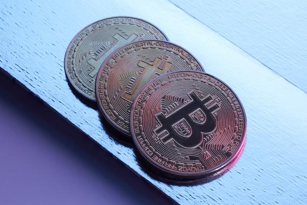 Золотые биткойны, изолированные на синем фоне крупным планом с копией пространства, концепция роста и падения криптовалюты