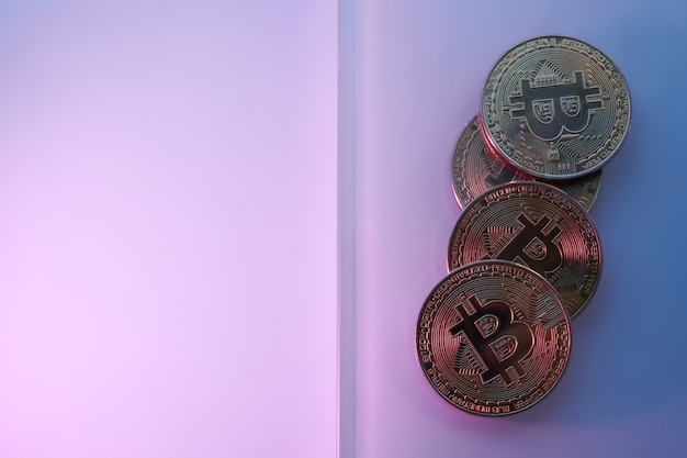 Золотые биткойны, изолированные на неоновом синем розовом фиолетовом фоне крупным планом с копией пространства, концепция роста и падения криптовалюты
