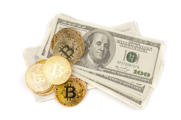 Golden bitcoins of new digital money on banknotes of one hundred dollars.