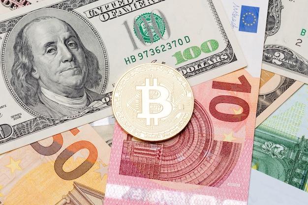 골든 비트코인은 전통적인 달러와 유로를 배경으로 하는 새로운 가상 화폐입니다. 매크로 사진입니다.