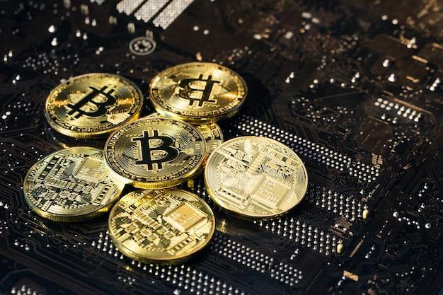 Золотые биткойны. новые виртуальные деньги. майнинг золотых биткойнов. монеты биткойнов, изолированные на фоне материнской платы.