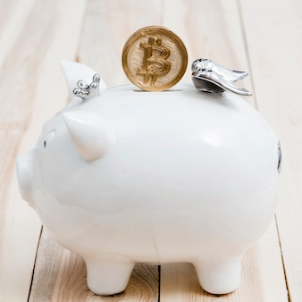 Golden bitcoins over the slot of white piggybank on wooden table