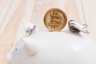 Golden bitcoins over the slot of white piggybank