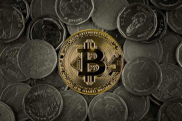 Golden bitcoins on pile of many coins.