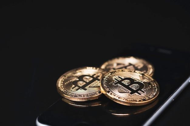 검은 배경으로 스마트 폰에 황금 bitcoins 더미. 블록 체인 및 디지털 암호화 통화 교환 개념.