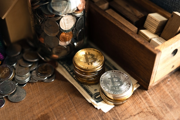 Golden bitcoins placed on a wooden desk in the house.