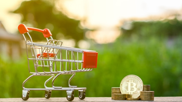 Golden bitcoins and a shopping cart in a golden coins stack on the table.