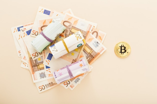 Golden bitcoins with euro banknotes as a background.