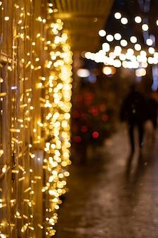 夜の街の夜のクリスマスの花輪のライトと金色のぼやけた背景