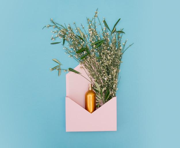 Золотая бутылка с травами и цветами в розовом конверте на синем фоне. вид сверху