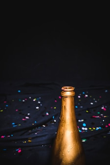 Golden bottleneck with confetti