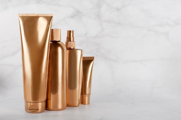 Золотые бутылки, косметические продукты на мраморной поверхности